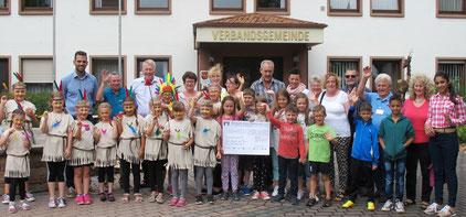 """Die Vertreter der drei Organisatoren, einige Ferienspielkinder, Bürgermeister Abstein und einige  """"Abspeck-Teilnehmer"""" waren bei der symbolischen Scheckübergabe der Volksbank-Aktion zugegen."""
