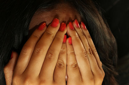 Eine Frau mit Händen vor ihren Händen vor dem Gesicht als Ausdruck der Angst