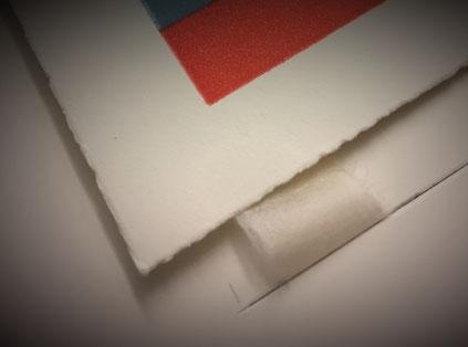 Einrahmung (Reversibel Fixierung, Falz durch den Trägerkarton durchgezogen. Fixierung der Falze auf der Rückseite )