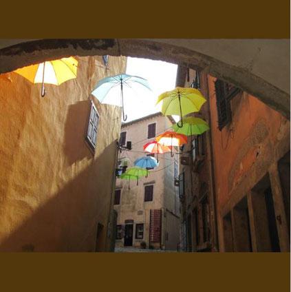 """Dieses Bild zeigt bunte Regenschirem in einer Altstadt. Diese können an den Film """"Mary Poppins"""" erinnern."""