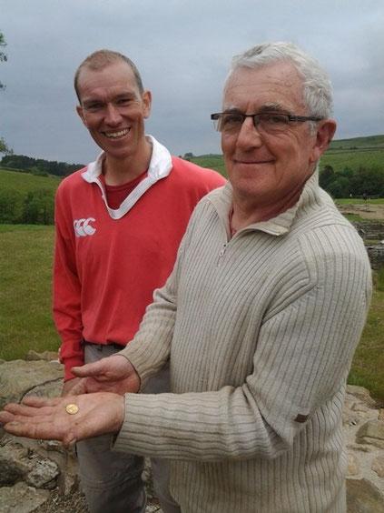 Directeur adjoint des fouilles Justin Blake (à gauche) avec Marcel Albert (à droite) tenant la pièce de monnaie. Vindolanda Trust