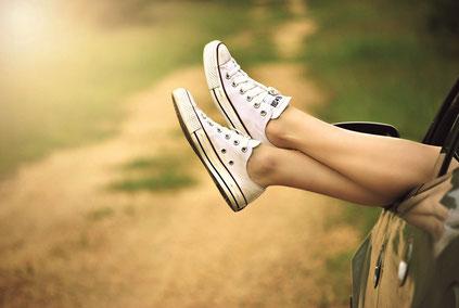 Beine mit Turnschuhen, entspannt aus Autofenster hängend