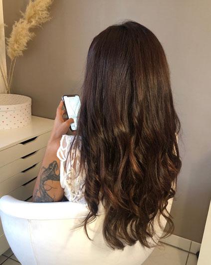 Cette photo représente une femme de dos qui regarde son smartphone et qui vient de recevoir une pose d'extensions de cheveux naturels chatains jusqu'en bas du dos.