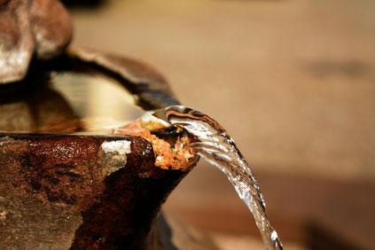 Wasserstrahl aus einem Steingefäß