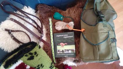 """Zwei Lederhalsbänder mit passender Leine, ein Kleeblatthalsband aus Biothane, zwei Dummybälle, das Buch """"Jagdhund ohne Jagdschein"""" auf dem Fell, die Dummyweste und die beiden Vetbeds."""