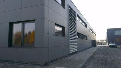 Bürogebäude mit hinterlüfteter Faserzementbekleidung sowie Lüftungslamellen