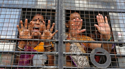 Kvinder råber slogans fra en politibil, efter de er blevet anholdt i forbindelse med strejkedemo i  Ahmedabad,  d. 2 september