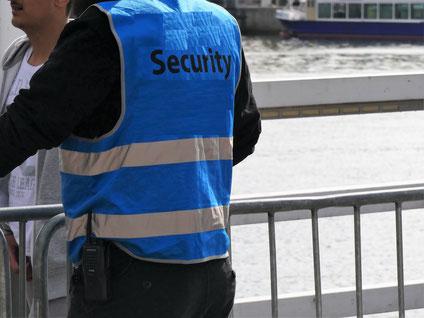 Sicherheits-Mitarbeiter mit weißem Schriftzug SECURITY auf dem Rücken einer blauen Warnweste vor einem Absperrgitter mit Menschen und Wasser dahinter (Hörnbrücke Kiel zur Kieler Woche)