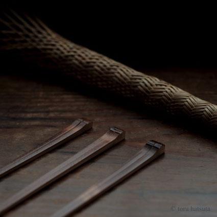 削りかけの煤竹箸と編みかけの竹籠