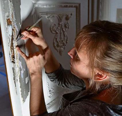 Britta Dierig löst mit einem Skalpell die einzelnen Farbschichten von der Holztür im Prinzenzimmer des Prinzenpalais Oldenburg (Foto: Katrin Zempel-Bley)