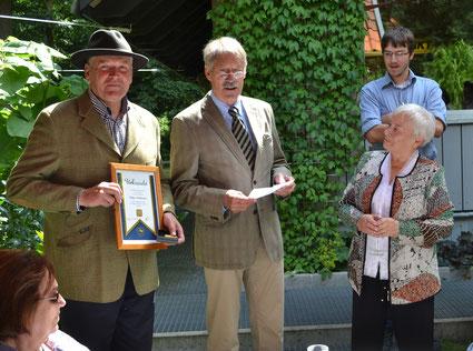 Heinz-Peter Schwingen hält die Urkunde und die Verbandsplakette in Gold bereit, während Horst-Axel Ahrens Helga Tiedemann an ihrem 80. Geburtstag Dank sagt für ihr herausragendes ehrenamtliches Engagement.