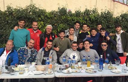 Imagen de 15 hombres de 20 años y cuatro de diferentes edades sentados junto a una mesa celebrando el triunfo de un partido.