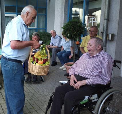 Chorobmann Werner Kuch überreicht Ehrenchorleiter Heinz Funk einen Geschenkkorb
