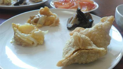 右手前がサモサ、左が中に入ってるもちキビポテト、奥がレンコンとワカメの煮もの。
