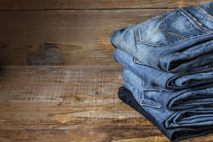 pile de plusieurs pantalons jeans pliés sur un plancher en bois