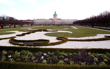Barockgarten mit Blick auf das Schloss Charlottenburg im März. Gut erkennbar sind die Broderien (Ornamente) gestaltet aus Buchsbaum, farbigem Kies und Rasen als Muster, umrandet von Blumenrabatten. Foto: Helga Karl