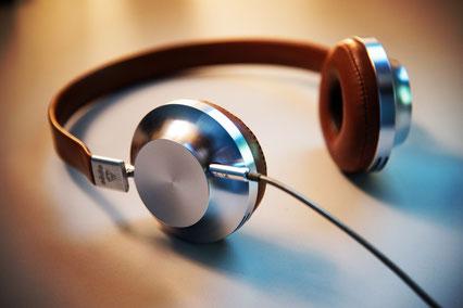 Ein Kopfhörer mit silbern gländzenden Muscheln liegt auf dem Tisch.