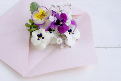 ピンクの封筒からのぞくパンジーのミニブーケ。