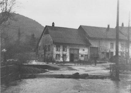 """Überschwemmung im Oberdorf: Schneeschmelze und gleichzeitiger Regen liessen die Bäche über die Ufer treten. Das Haus der Familie Husner, """"Muurers"""", steht ganz im Wasser. (Foto: Arthur Brogle, 3.3.1956)"""