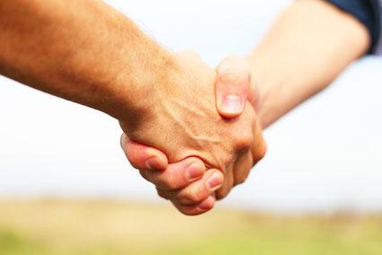 Ein Handschlag zweier Menschen als Symbol für eine gegenseitig akzeptierte Vereinbarung.