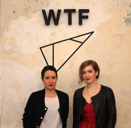 """Christina Gassen und Marie Sophie Nübling stehen unter einem Wandlogo mit den Buchstaben """"WTF"""""""