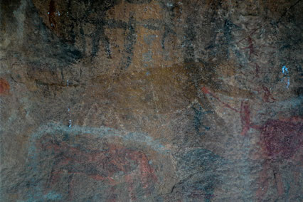 Brwon bushmen painting of a lion or cheetah, four warriors in red with spears to its right, fighting it.