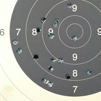 Zielscheibe (Ausschnitt) mit vielen Durchschußlöchern in den Ringen 10, 9, 8, 7, 6