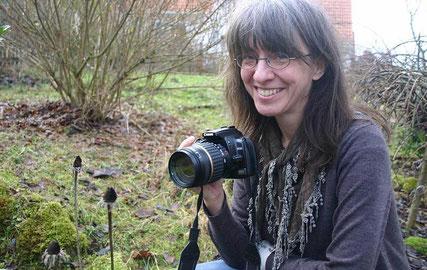 Frau mit Kamera im Garten