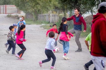 Bastian playing football in the streets of Kara-Kool