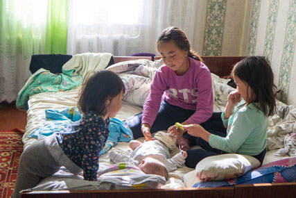 The elderly sisters taking care of the newborn