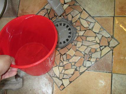 """Der Bodensiphon ist als Gully in einer tiefen Mulde eingelassen, damit sich ein """"Becken"""" bildet. Um den Bereich fliesen zu können, habe ich Bodenfliesenreste zertrümmert und daraus ein Mosaik gefliest."""