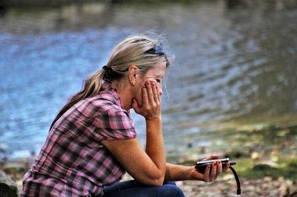 Sad woman by lake.