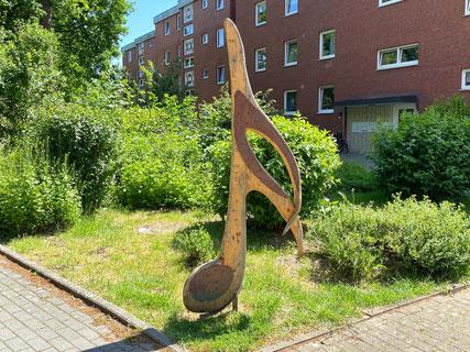 Mehrere lebensgroße Plastiken aus Holz, wie Notenschlüssel, Note und Gandhi-Zitat in Bremen-Arsten auf dem Gelände der Brebau-Wohnbebauung (Foto: 05-2020, Jens Schmidt)