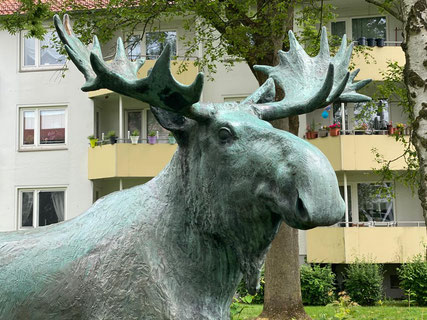"""Das Kunstwerk """"Elch"""" steht in Bremen-Kattenesch, Ecke Höxterstraße / Münsterstraße auf einer Wiese hinter einer Reihenhausbebauung. Es ist eingerahmt in einen Kreis verschiedener Büsche und steht unter einem Baum (Foto: 05-2020, Jens Schmidt)"""