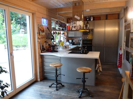 Open plan kitchen with table and floors from recycled timber