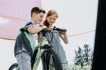 Zwei Kinder stehen an einem R Raymon Kinder e-Bike