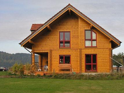 Blockhaus mit roten Fensterramen - Blockhäuser, Holzhäuser, Holzbau, Planung, Blockhausbau, Einfamilienhäuser, Fenster, Türen, Holzfenster, Lüftungsfenster, Insektenschutz, Hausplanung, Kunststofffenster Bauplan