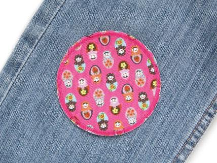 !B: runder Bügelflicken auf Jeanshose gebügelt als pinker Jeansflicken mit vielen kleinen bunten Matroschkas