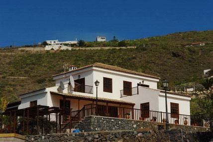 Bild und Link: Ansicht vom Haupthaus mit den Bergen im Hintergrund und dem Link zur Beschreibungsseite.