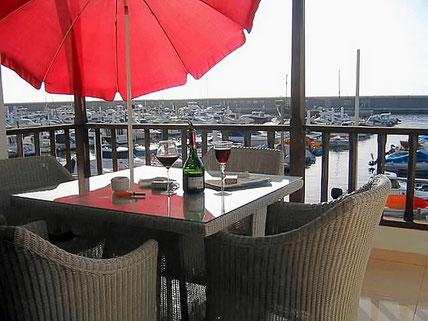 Balkon mit rotem Sonnenschirm und Blick auf den Hafen von Los Gigantes