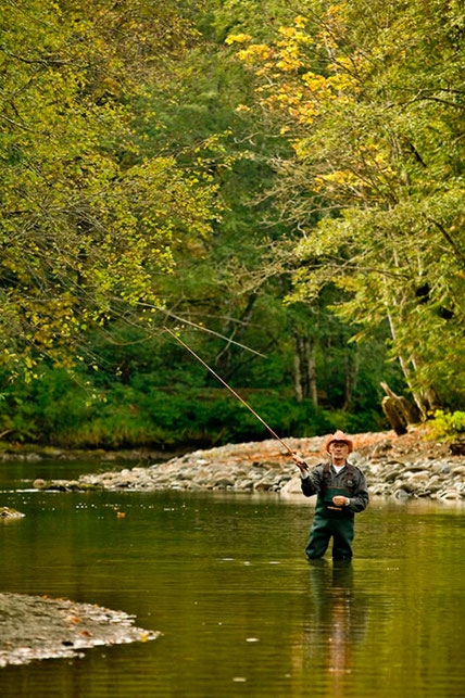A man standing in the Oyster River fly fishing.