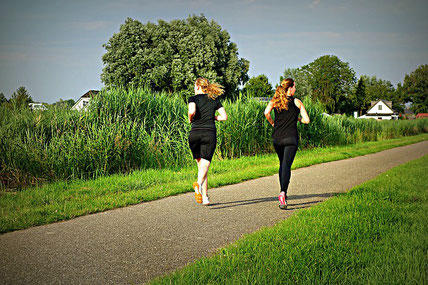 2 women running on a sunny day