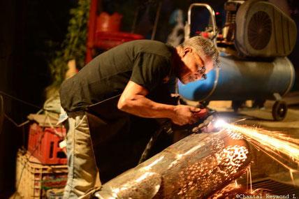 Abdel Ali, l'artiste en train de faire de la découpe au laser sur une sculpture en fer