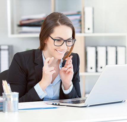 Geschäftsfrau sitzt lächelnd an ihrem Laptop im Büro und kreuzt die Finger