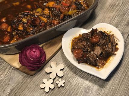 Ofenhexe von Pampered Chef mit geschmorten Nackensteaks und Gemüse auf einem Teller angerichtet und mit einer Blume dekoriert