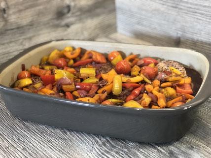 Ofenhexe von Pampered Chef auf Arbeitsplatte mit Nackensteaks und Gemüse gefüllt