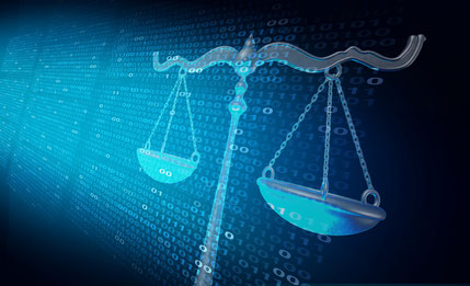 Scales of justice in front of dark computer screen showing lines of binary code fade out into the back