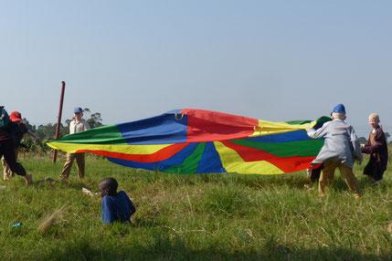Eigentlich macht man mit diesem Regenbogentuch ganz friedliche Spiele, unsere Kids haben damit aber lieber Fange gespielt und den Gefangenen dann in dem Tuch eingerollt ;)