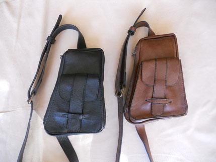 """Sacoche """"holster"""", porté travers, cuir noir ou marron (taureau à effet), trois poches, doublé croûte de cuir noir, bandoulière réglable. 115 euros."""