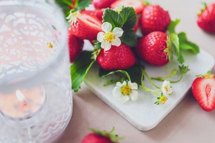毛糸で編まれたカラフルなハートたち。毛糸が入れられたバスケットと編み棒。
